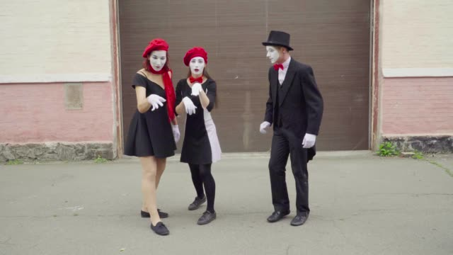 Three funny mimes do imitation on city street Company of three mimes, man and women in black dress do perfomance in the city. One girl imitate fly with her hand and two her friends try to catch it. Performance of street artists. greasepaint stock videos & royalty-free footage