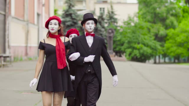 Three funny mimes play scenes in the city street Company of three mimes, man and women in black dress do perfomance in the city. Actor and actress walk swowly hand in hand, and third girl walks behind ans admire their couple, sending kisses to both. greasepaint stock videos & royalty-free footage