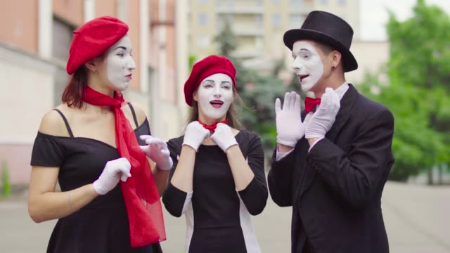 Three funny mimes play scenes in the city street Three funny mimes act in the city street. Company of three mimes, man and women in black dress do perfomance in the city. greasepaint stock videos & royalty-free footage
