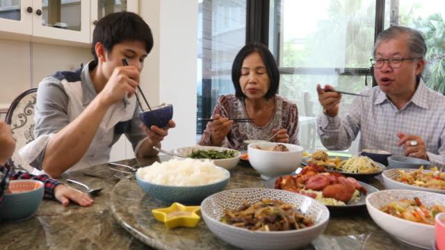 tre generationens asiatisk familj servering och äta lunch hemma - kinesiskt ursprung bildbanksvideor och videomaterial från bakom kulisserna
