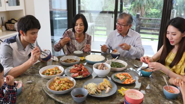 drei generationen asiatische familie serving und essen mittagessen zu hause - chinesischer abstammung stock-videos und b-roll-filmmaterial