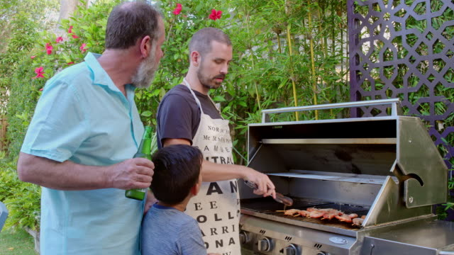 Three generation Australian family men sharing barbecue moments in the summer video