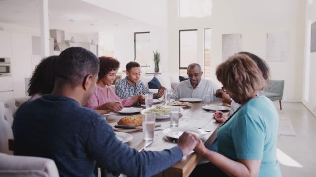 trzypokoleniowa czarna rodzina siedząca przy stole trzymając się za ręce i mówiąca łaskę przed posiłkiem - modlić się filmów i materiałów b-roll