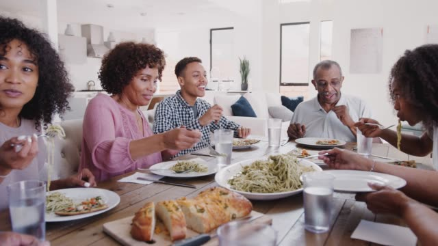 Three generation black family sitting at dinner table serving spaghetti, panning shot video