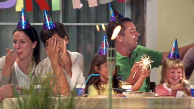 HD: Three Generation Family Celebrating Birthday HD1080p: PANNING shot of a three generation family singing and having fun while sitting at patio table and having a backyard birthday party. cousin stock videos & royalty-free footage