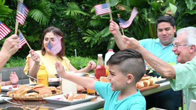 Three generation family celebrating Fourth of July Hispanic family having outdoor meal waving stars and stripes American flags having fun fourth of july videos stock videos & royalty-free footage