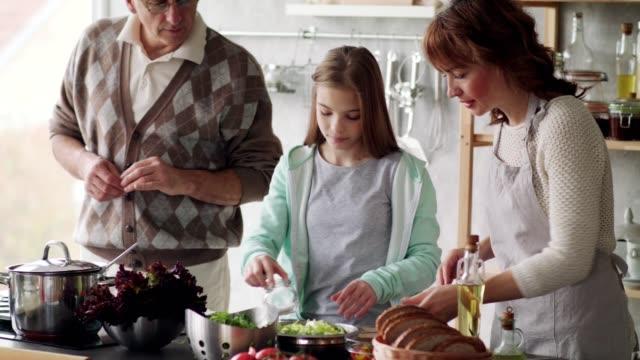 stockvideo's en b-roll-footage met drie generatie familie koken samen - oil kitchen