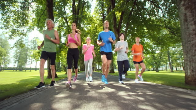 SLO MO TS Three generation family jogging in a beautiful park video