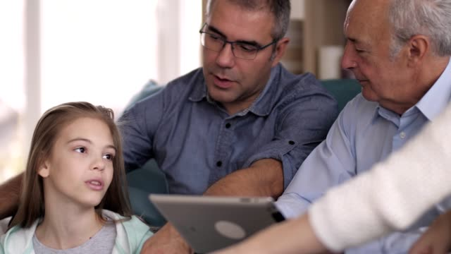 Three generation family relaxing at home Caucasian girl, her father and grandfather are spending time together in the living room. Senior man is using digital tablet. granddaughter stock videos & royalty-free footage