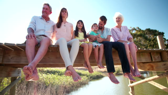 Three generation family relaxing together on a jetty video