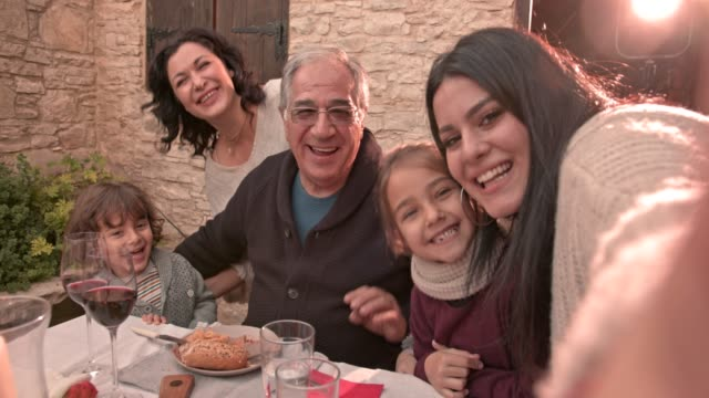 Three generation family taking selfies at lunch video
