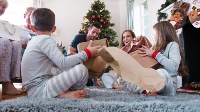 tre generation familj klädd i pyjamas i loungen på hem öppning gåvor på juldagen - christmas gift family bildbanksvideor och videomaterial från bakom kulisserna