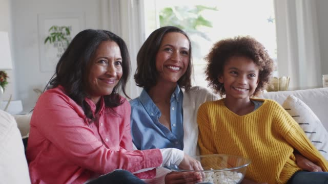 Three generation female family group sit watching TV, laughing and eating popcorn, close up Three generation female family group sit watching TV, laughing and eating popcorn, close up granddaughter stock videos & royalty-free footage