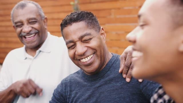 vídeos de stock, filmes e b-roll de três gerações de homens pretos da família que riem junto ao ar livre, fim acima - origem africana