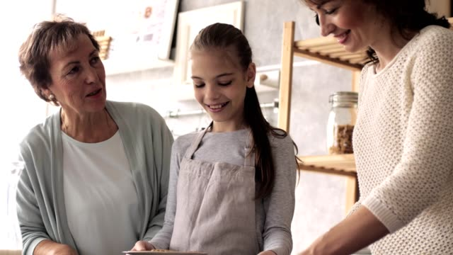 Three generations of women serving cookies Senior woman, girl, and mid adult woman are arranging freshly baked cookies on a plate at the kitchen counter. granddaughter stock videos & royalty-free footage