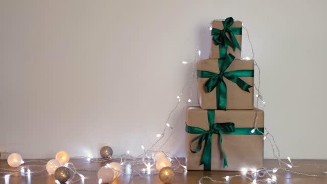 vídeos y material grabado en eventos de stock de tres cajas de regalo con cintas verdes decoradas con luz. - christmas stocking
