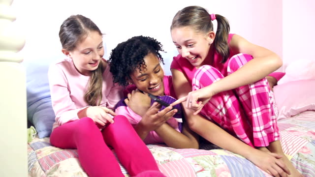 three girls at sleepover laughing at mobile phone - предподростковый возраст стоковые видео и кадры b-roll