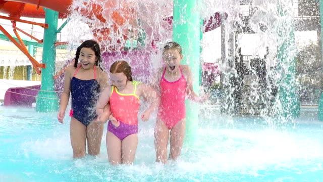Three girls at water park walk under fountain