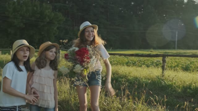 Three girls children with bouquet of flowers show finger on the road
