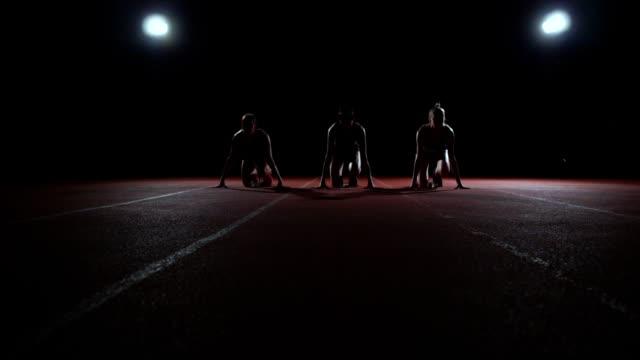 işıklar ışığında yarışmada yarış başlatmak ve bitirmek doğru çalıştırmak için başlangıç yastıkları siyah giysili üç kız bulunmaktadır - başlama çizgisi stok videoları ve detay görüntü çekimi