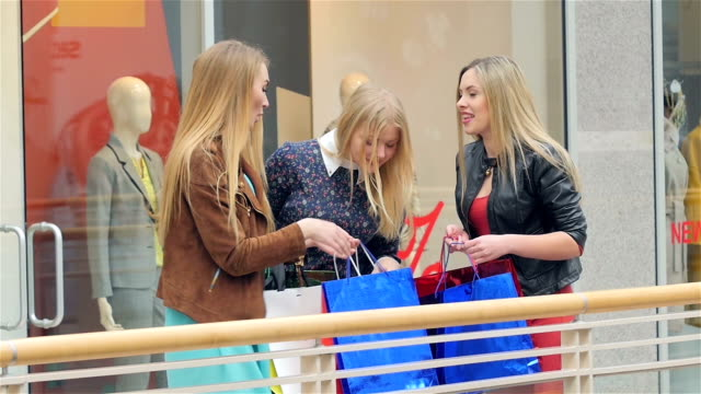 Three girls on a shopping: meeting friends. Slow motion