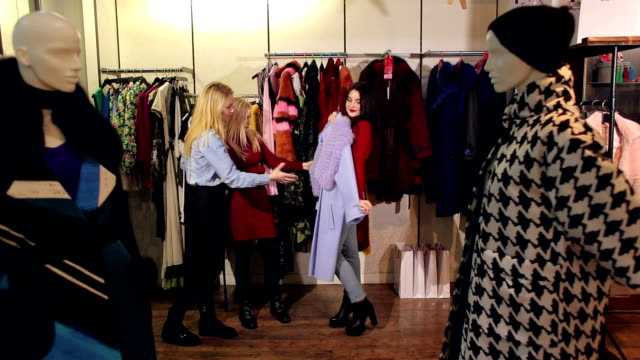 Video Three girls walk in a clothing store, they look at clothes and try it on.