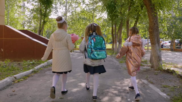 Three girls with flower bouquets walking to school, back view Three schoolgirls with flower bouquets walking to school, back view. Female classmates going back to school together in slow motion. Happy girls with backpack going to college, rear view back to back stock videos & royalty-free footage