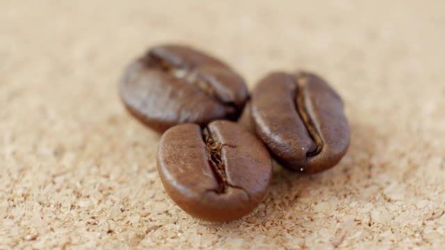 Bидео Three grains of coffee close-up on brown background