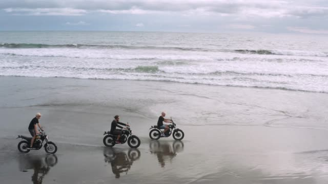 Three handsome hipster men riding modern custom motorcycle cafe racer on the black sand beach near the ocean. Adventure travel concept. Surfing spot with ocean waves. Aerial shot. 4k