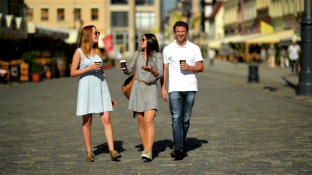 Three Happy Friends Drinking Coffee while Walking around the City. Full Height Portrait of Two Girls and One Boy with Beverages in the Hands video