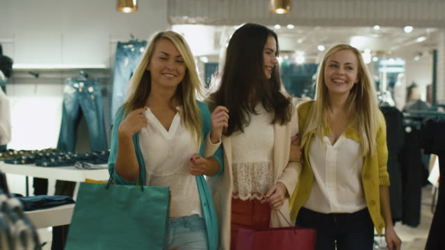 three happy girls are walking through a clothing store in colorful garments. - личный аксессуар стоковые видео и кадры b-roll