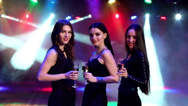 Tres niñas felices con champagne en un club nocturno. - vídeo