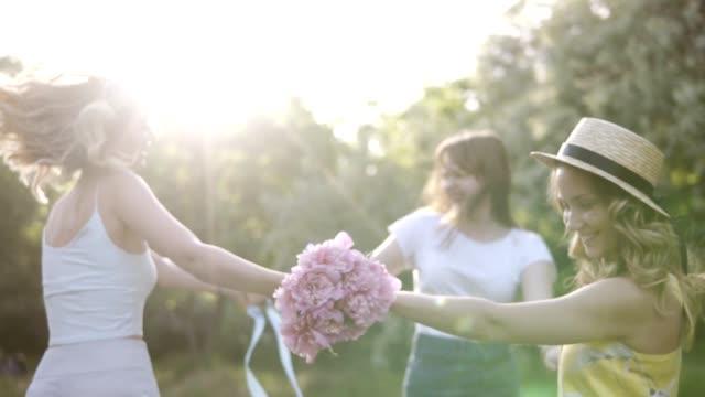 3 人の笑顔は、幸せな女の子サークルで踊って日当たりの良い草原。一緒に幸せな時間 ビデオ