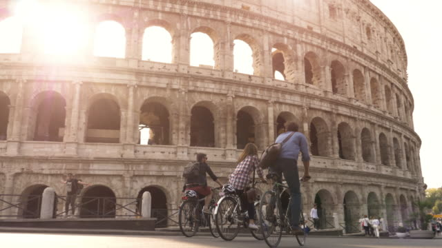 三快樂的青年朋友騎自行車背包在羅馬競技場在陽光明媚的一天慢鏡頭 steadycam - 旅遊業 個影片檔及 b 捲影像