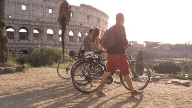 三愉快的年輕朋友遊客與自行車和背包在羅馬競技場到達山在日落與樹慢運動 steadycam - 旅遊業 個影片檔及 b 捲影像