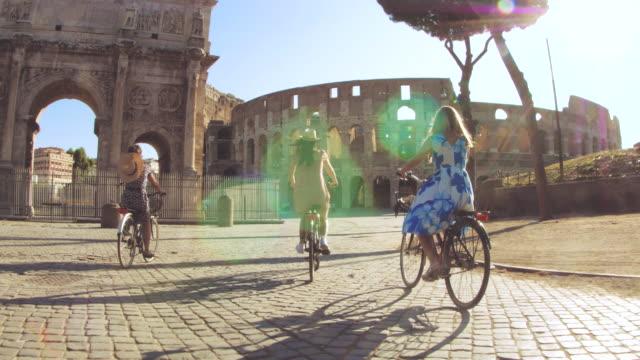 three happy young women friends tourists riding bikes at colosseum in rome, italy at sunrise. - amicizia tra donne video stock e b–roll