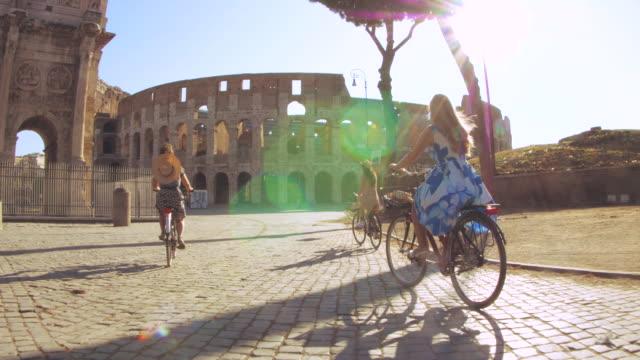 vidéos et rushes de trois jeunes femmes heureuses touristes d'amis conduisant des vélos au colisée à rome, italie au lever du soleil. - europe