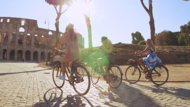 vídeos de stock e filmes b-roll de three happy young women friends tourists riding bikes at colosseum in rome, italy at sunrise. - amizade feminina