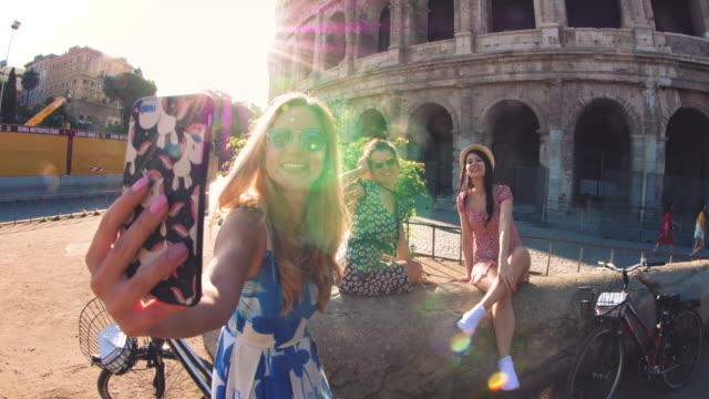 drei glückliche junge frauen freundet touristen mit fahrrädern, die videos mit smarphone am kolosseum in rom, italien bei sonnenaufgang. - storytelling videos stock-videos und b-roll-filmmaterial