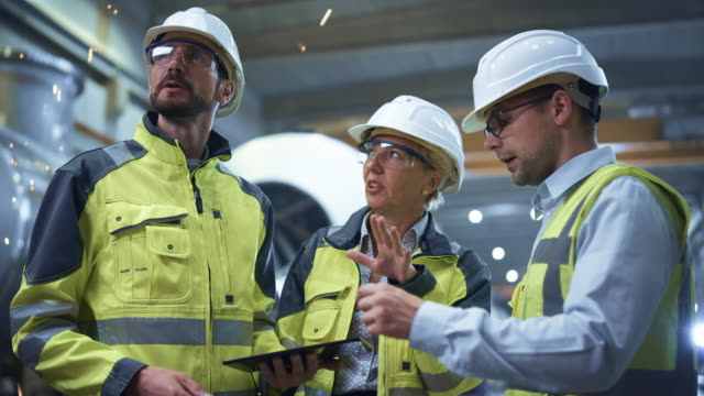 Three Heavy Industry Engineers Stand in Pipe Manufacturing Factory, Use Digital Tablet Computer, Have Discussion. Large Pipe Assembled. Design and Construction of Oil, Gas and Fuels Transport Pipeline Three Heavy Industry Engineers Stand in Pipe Manufacturing Factory, Use Digital Tablet Computer, Have Discussion. Large Pipe Assembled. Design and Construction of Oil, Gas and Fuels Transport Pipeline oil industry stock videos & royalty-free footage