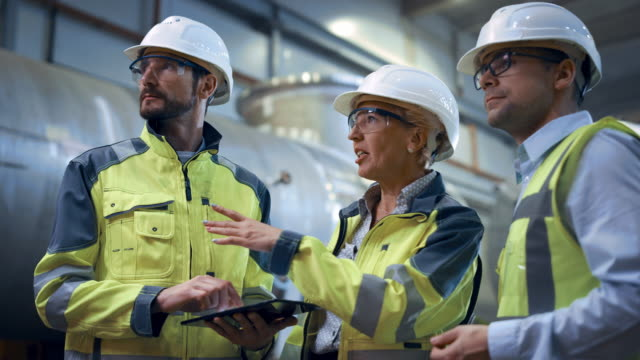 three heavy industry engineers stand in pipe manufacturing factory, use digital tablet computer, have discussion. large pipe assembled. design and construction of oil, gas and fuels transport pipeline - produkować filmów i materiałów b-roll