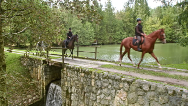CS Three horseback riders trotting across a lake bridge