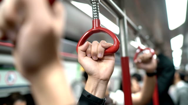Three Human Hands Holding Handrail or Grip Straps in Subway or Train Three Human Hands Holding  Handrail in Subway or Train. The Shot is changing focus to each hand underground stock videos & royalty-free footage