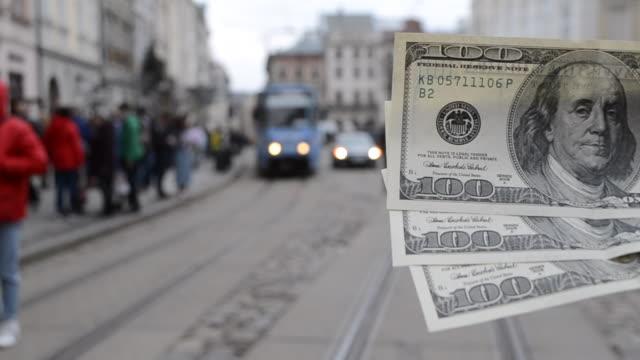 vídeos de stock, filmes e b-roll de 300 notas de dólar em fundo desfocado da antiga rua europeia antiga - bico