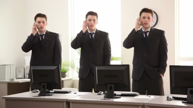 Three identical businessmen talking on phones video