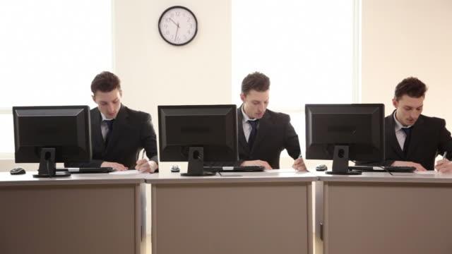 tre uomini d'affari che lavorano alla scrivania identiche - coinvolgimento dei dipendenti video stock e b–roll
