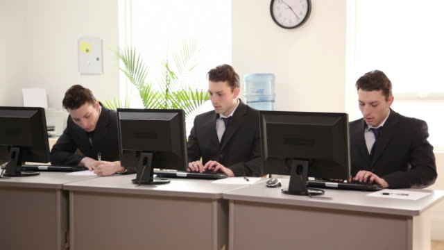Three identical businessmen working in office  employee engagement stock videos & royalty-free footage