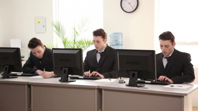 vídeos de stock e filmes b-roll de três idêntica a trabalhar no escritório - envolvimento dos funcionários