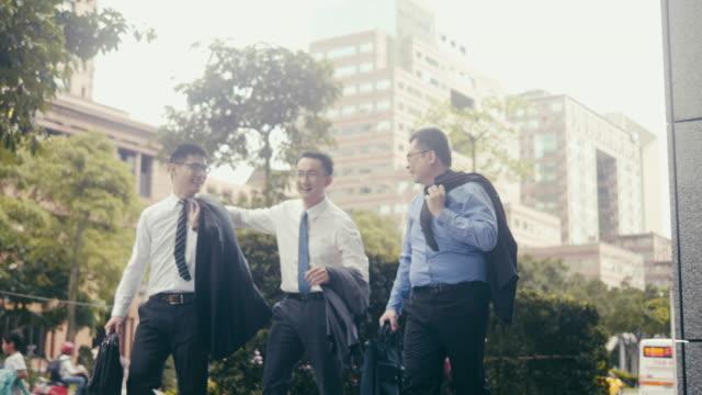 通りを歩きながら笑う3人のアジアのビジネスマン - 東アジア点の映像素材/bロール