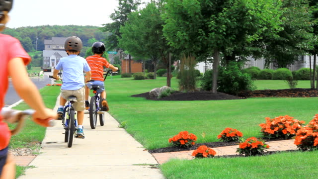 Three Kids Biking Away Three young children ride away on the sidewalks of a summer day in suburban, America. The joys of summer vacation and no school! americana stock videos & royalty-free footage
